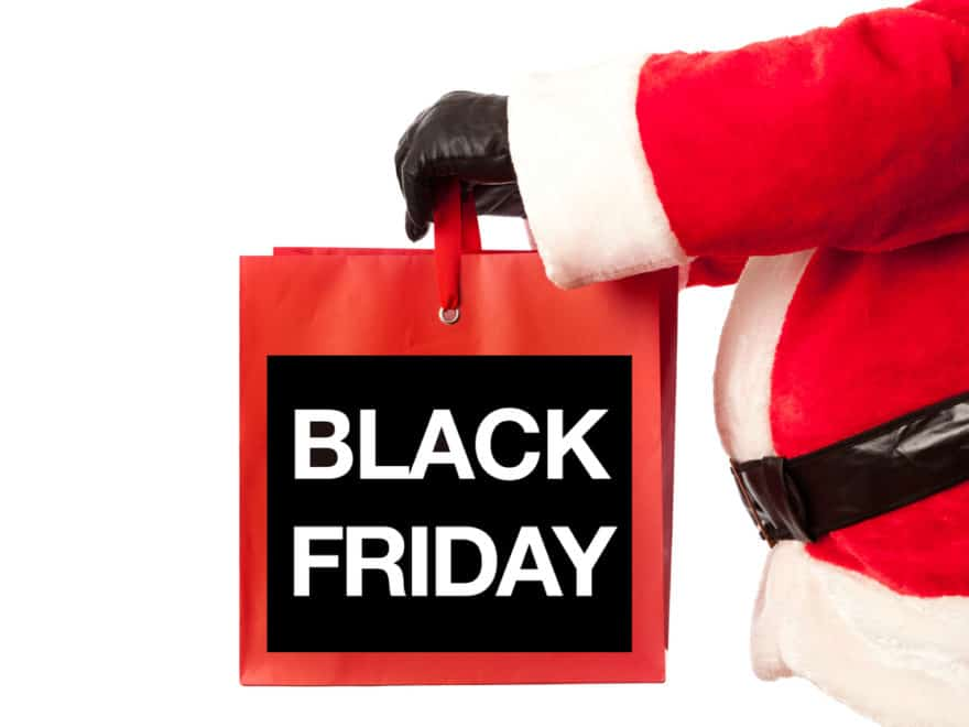Christmas Santa Claus with a Black Friday Shopping billboard sign presented on a white background. A happy Santa Claus pointing at a Black Friday sign, the biggest Christmas shopping day on the Friday after Thanksgiving. Photographed in vertical format, Isolated on a white background.