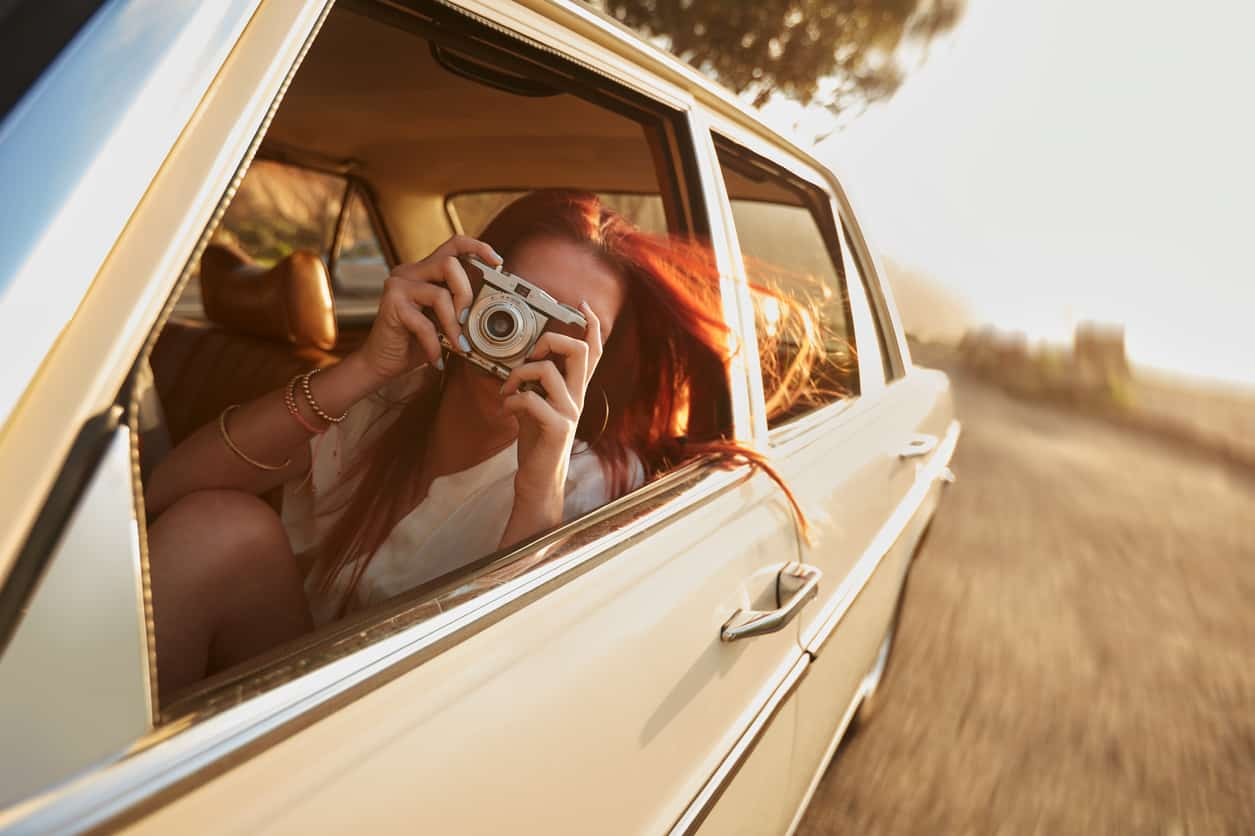 Shot of young woman taking photos while sitting in a car. Female capturing a perfect road trip moment.